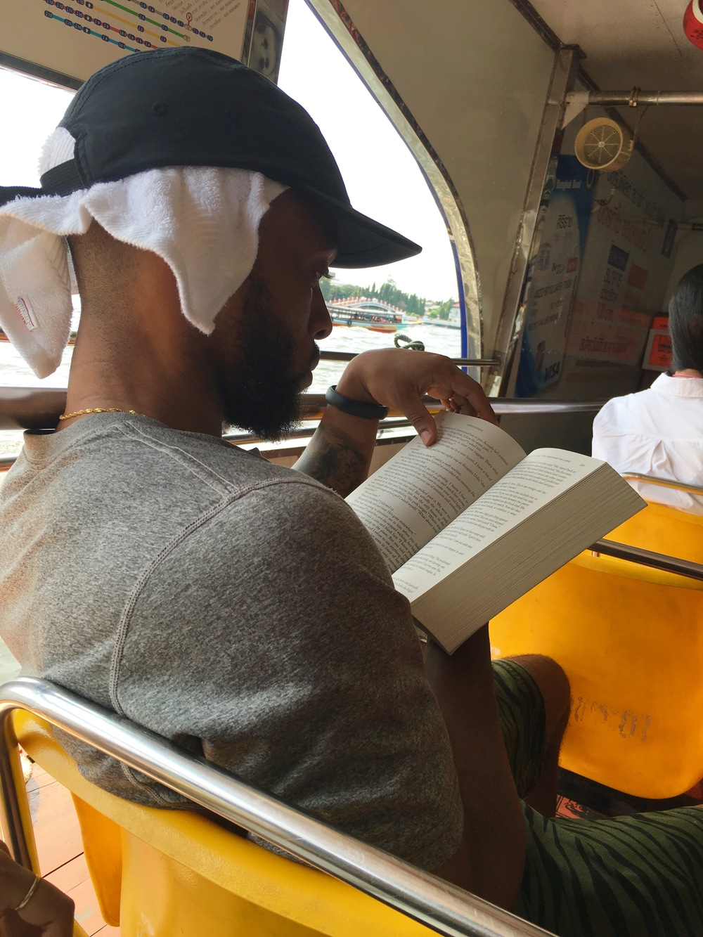 Reading while taking ferry to Grand Palace.