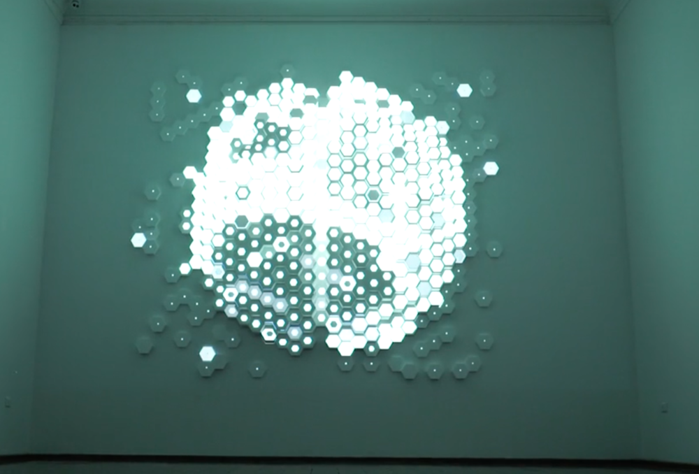 Hive Mind - The installation uses projection to map the glowing, synaptic impulses of a human mind onto an intricate hexagonal structure. Using data drawn from personal neurological scans...
