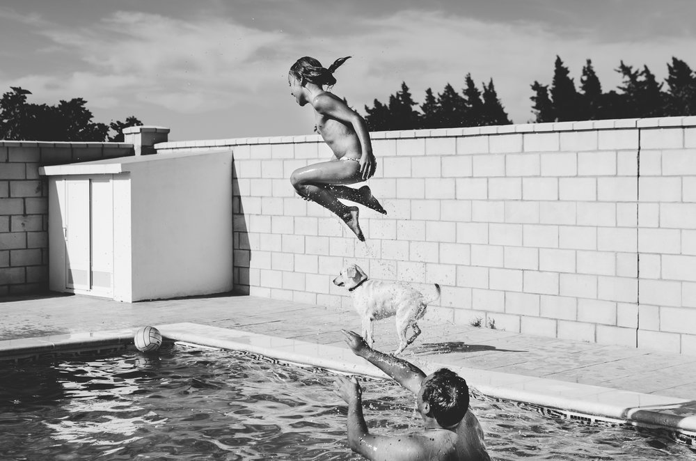 Girl jumping in the swimming pool in summer