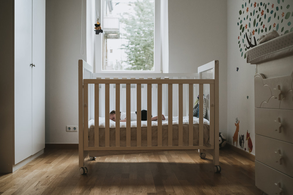Newborn baby in crib in bedroom.jpg