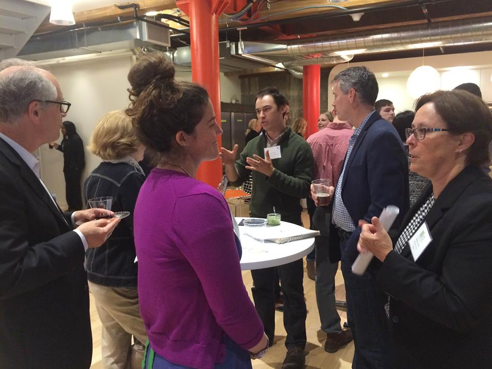 Lauren Valle (in purple sweater) and Max Rome (in green sweater at back) of Nu Ecological talk with potential mentors for the CleanTech Open accelerator.