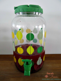 clear plastic tap with fifties-style pears and apples in yellow and green, with a green lid and green spout. filled with a dark pink/purple liquid