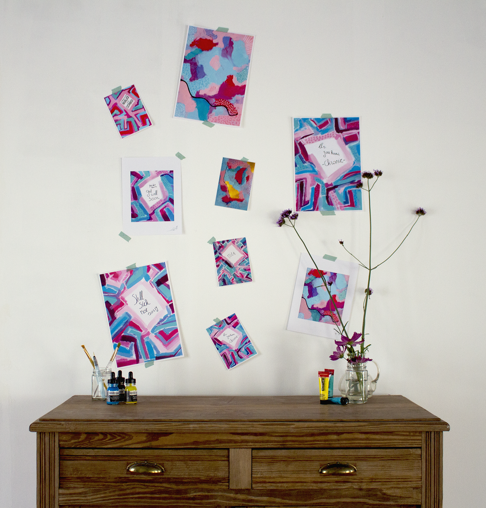Image: different prints taped to a wall with dark blue washi tape. All are in a blue/pink color scheme, some have writing on them, others are just abstract. Prints hanging over a brown wooden sideboard. There a different paint supplies (paint, ink brushes) and flowers on the sideboard.