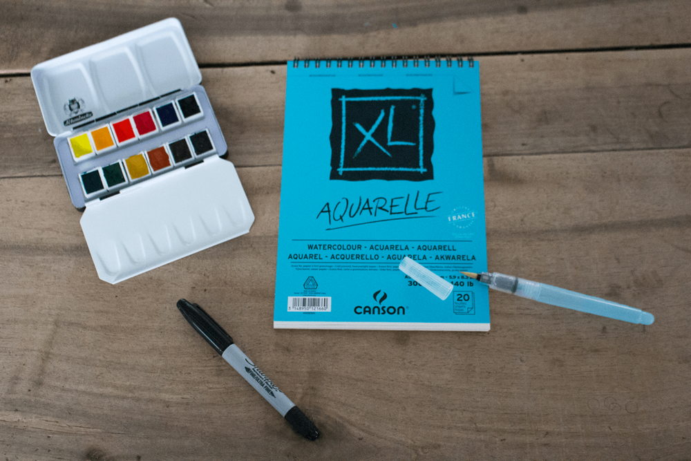 Image: supplies for craft project. On a wooden table, there are a sharpie marker, a watercolor set that's open so the paint colors are visible, in the middle there's a watercolor paper pad (spiral bound at the top), a water brush pen is