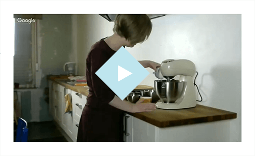 An image of a video, we see Sarah standing in the center, she wears a super cool purple dress, she's pouring something from a cup into a stand mixer.