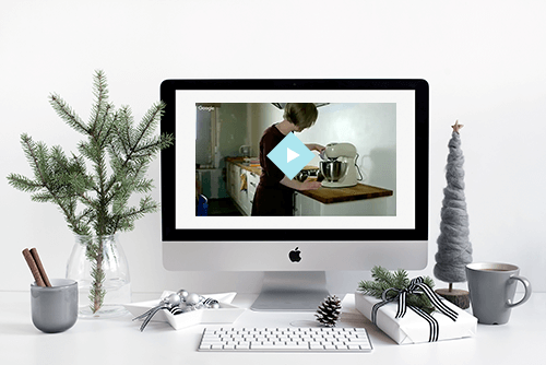 an image of a desktop computer displaying the workshop video. The area around the computer is decorated with christmas items; a gift, a mug with a cinnamon stick, evergreen branches in a vase, a felt christmas tree, baubles.. all in a grey/green color scheme
