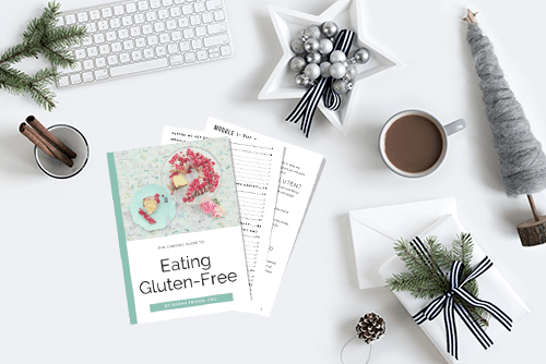 an image of a desk with printed pages of the eating gluten-free ebook. The area around the ebook is decorated with christmas items; a gift, a mug with a cinnamon stick, evergreen branches in a vase, a felt christmas tree, baubles.. all in a grey/green color scheme