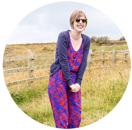 an image of sarah, she's wearing an awesome red and blue jumpsuit with a leaf pattern, a blue cardigan and brown clip-on sunglasses. She's standing in front of a field
