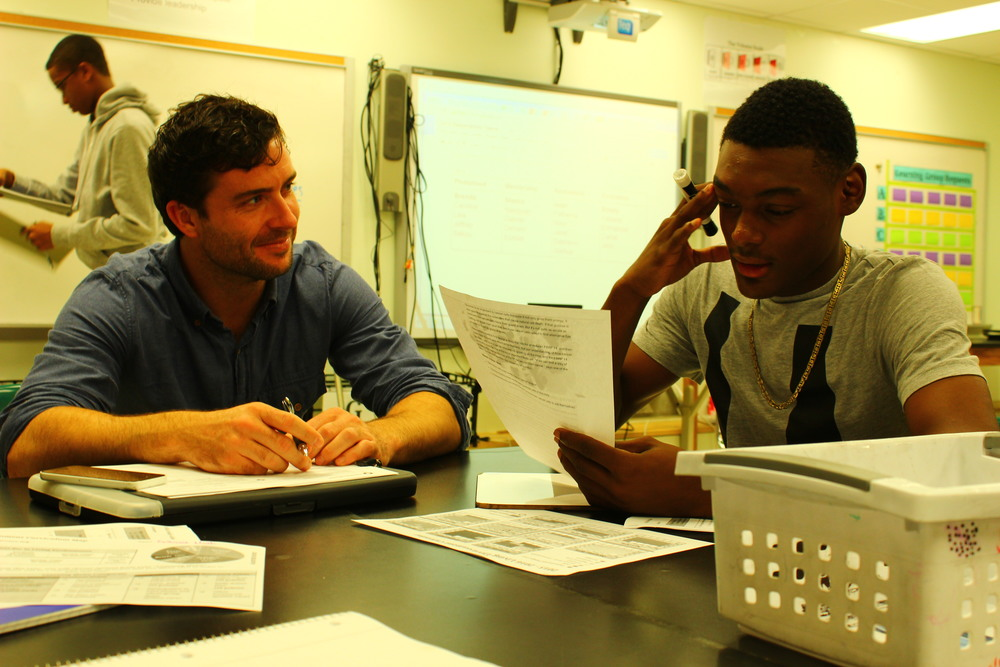 Teacher Tyler Lanker supporting junior Isiah Frazier in one of the many double teacher UAGC classrooms