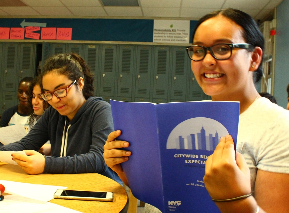 Sophomore Johancarla Taconas and members of the Keepers of the Culture reviewing the Citywide Behavioral Expectations (The Blue Book)