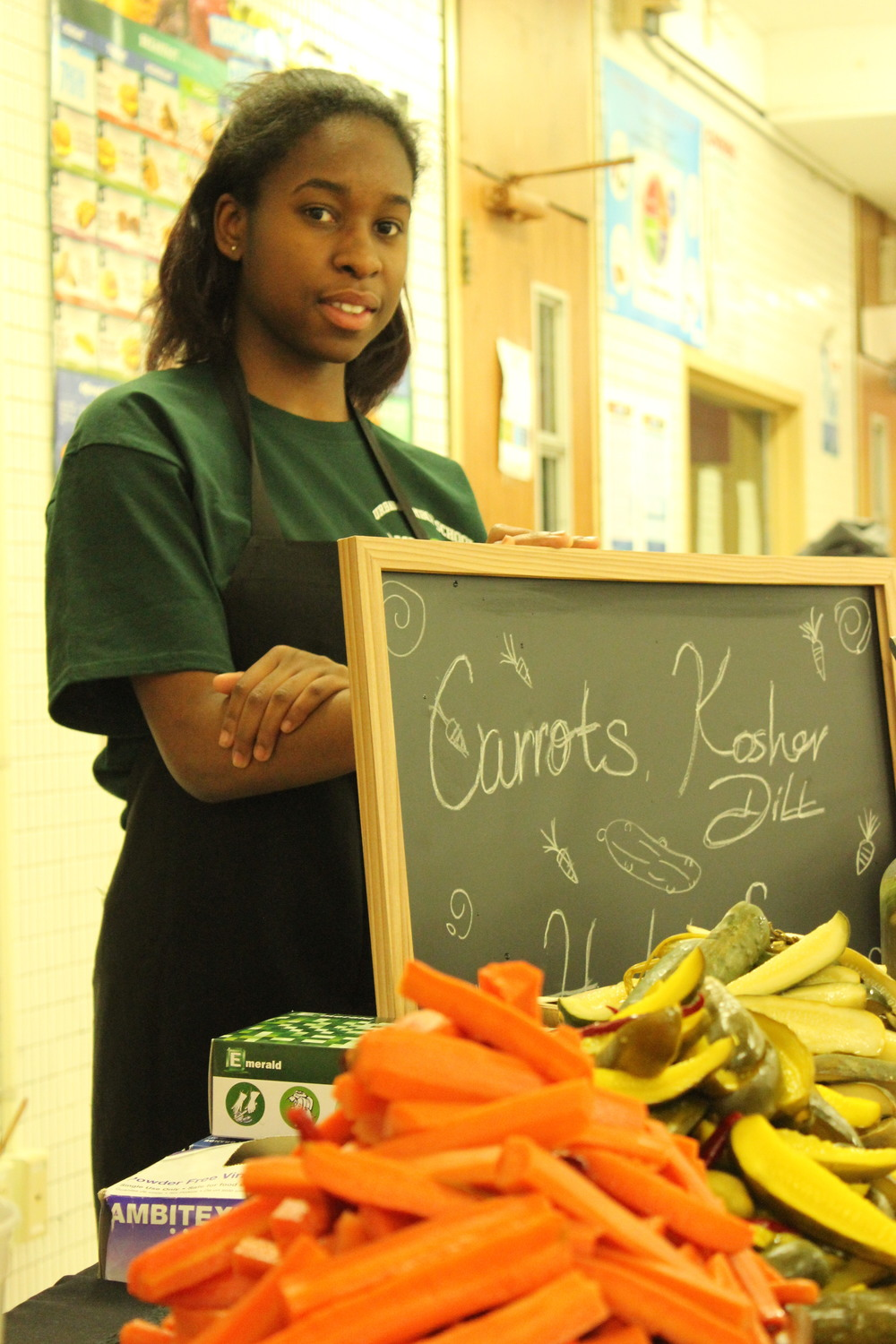 UAGC Student Shania Clarke, with pickled carrots and cucumbers ready for service