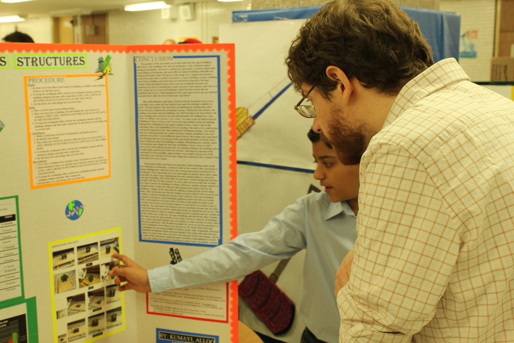 Science Expo participant explains experiment to UAGC physics teacher Chris Bohl
