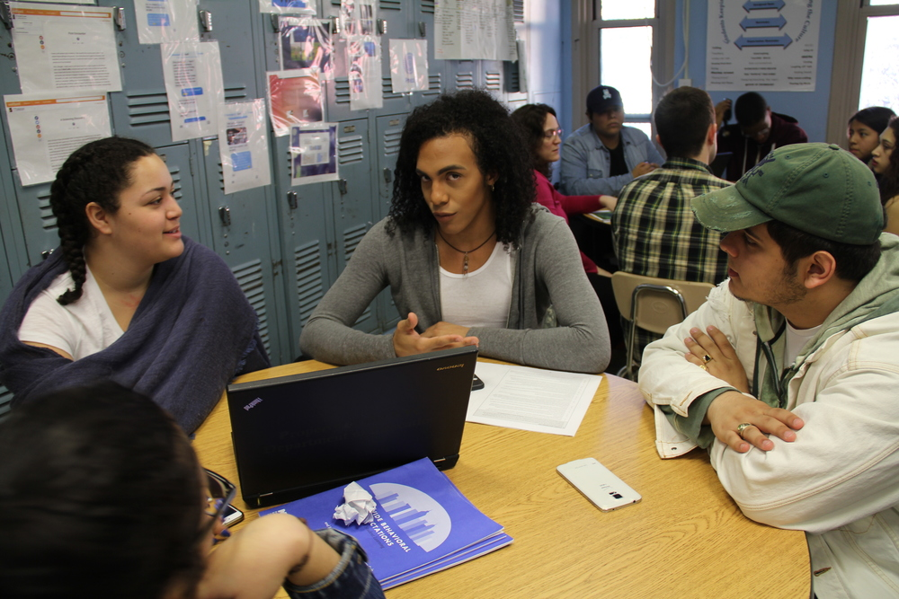 Paloma Parades Jaquez (right) and Brandon Aviles (left) meeting with Rolando Diaz III in a Keepers of the Culture meeting. Behind them, Counseling in Schools counselor works with another KOC group.