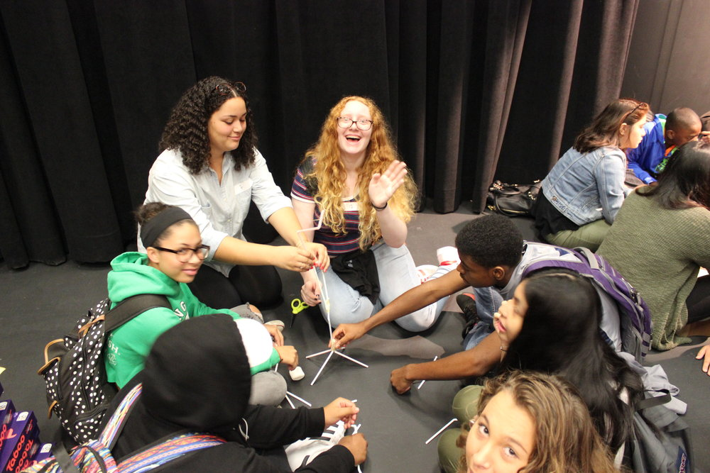 Alumni Paloma Paredes-Jaquez, current Hunter College student, laughs with a group of stumped students