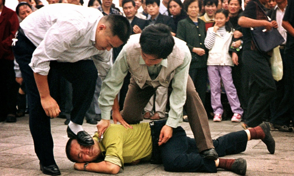 Police detain a Falun Gong protester in Tiananmen Square as a crowd watches in Beijing, in 2000. Photograph: Chien-Min Chung/AP