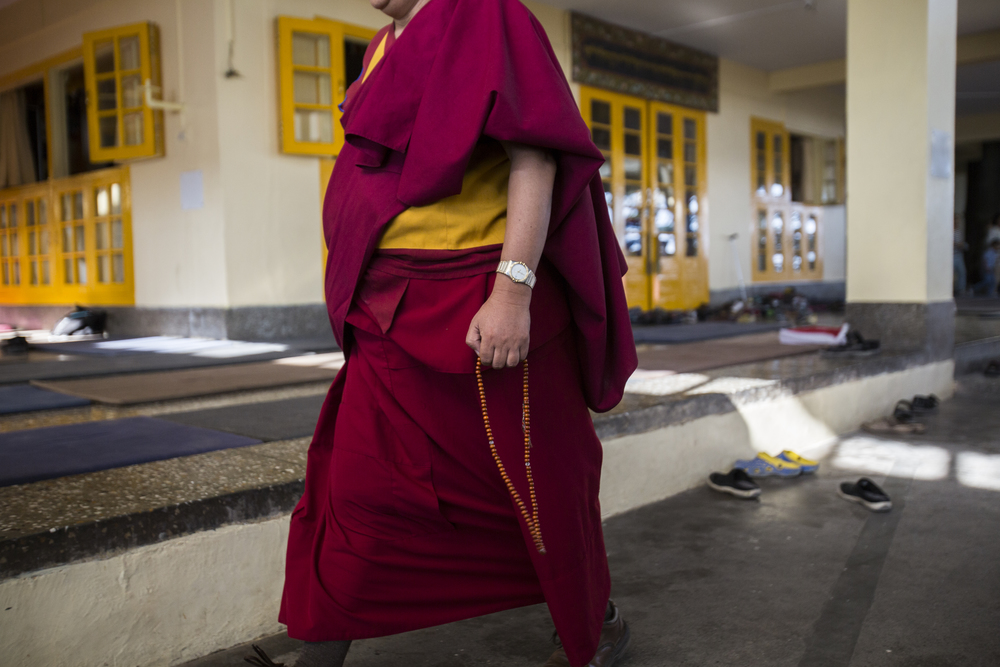 Monks can be seen continually walking the grounds here. Behind him are scattered shoes as worshippers have entered a Buddhist prayer room that features a large statue of Buddha.