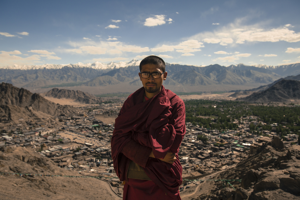 A Buddhist monk stands on the temple grounds overlooking Ladakh's capital city of Leh. You can see the city stretched out in the valley below him as well as the Himalayas behind him.