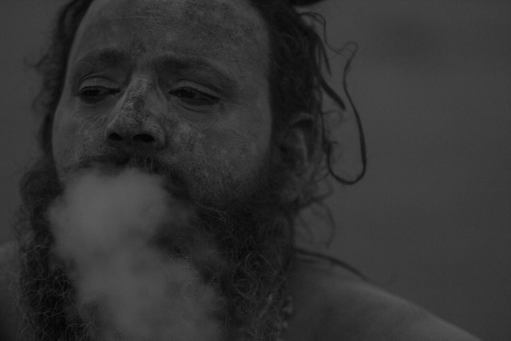 This man is a Sadhu, a group of people known for living very minimalistic lives. He is in Varanasi, known as a very spiritual place. Hundreds of bodies are cremated here to be near the Ganges River. In the hopes of achieving a profound spiritual experience, he has rubbed ashes all over his body and is smoking marijuana.