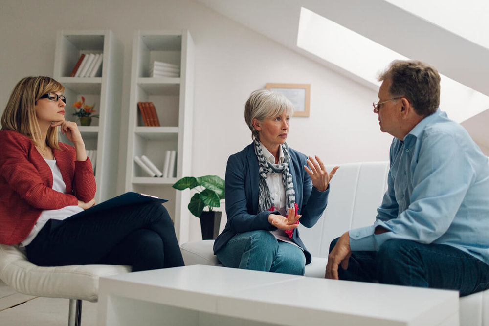 mature man and woman speaking with a counsellor