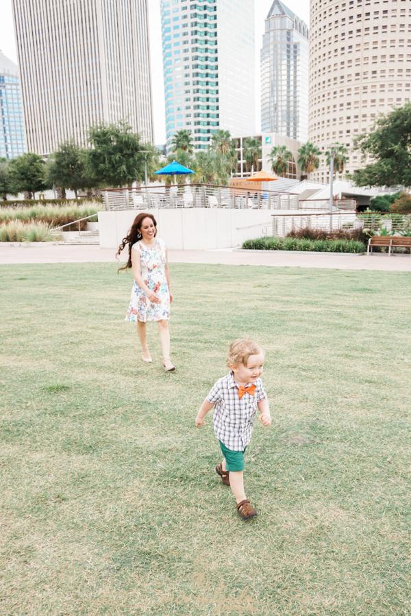 mom-chasing-baby, little-boy-giggles, tiny-joy, little-feet-running, orange-bowtie, grassy-field