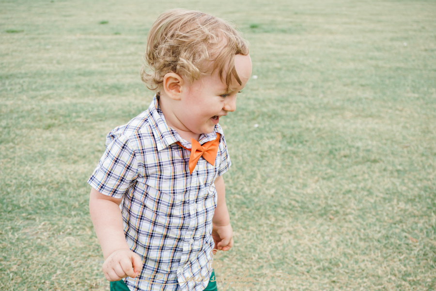 baby-boy-giggles, tiny-joy, little-feet-running, orange-bowtie, grassy-field