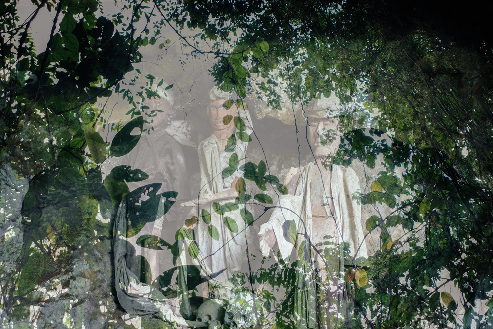 Double-exposure of tau-tau (effigies) against the view out from a cave.