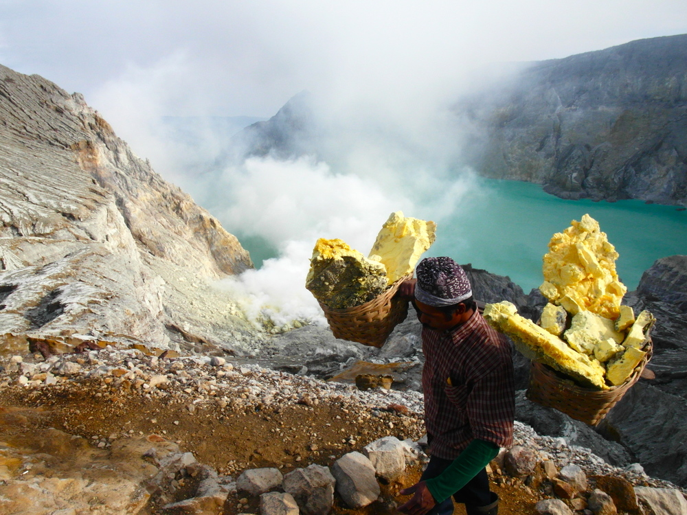 One of the many miners carrying his freshly-laden load down the volcano.