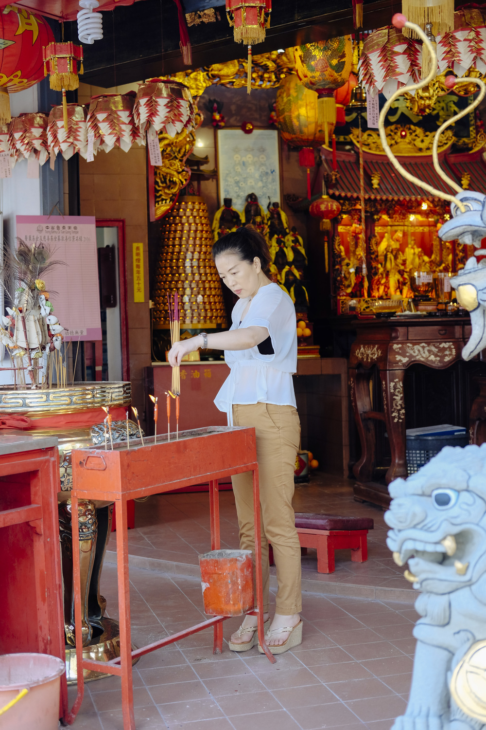 A devotee burns joss sticks at Qi Tian Gong, otherwise known as the Monkey God Temple to non-Chinese speakers.