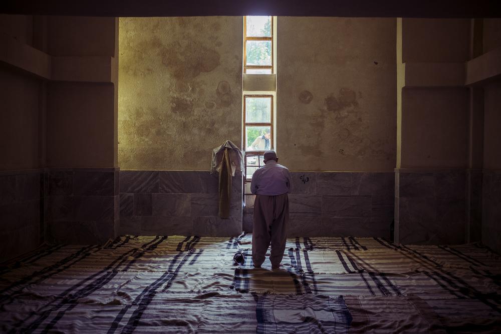 An aged man praying in the mosque near the Zrebar lake in Mariwan.