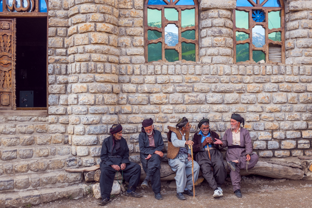 Men, dressed in the traditional Kurdish wear, waiting for the prayer call outside the mosque in Hawraman Takhte.