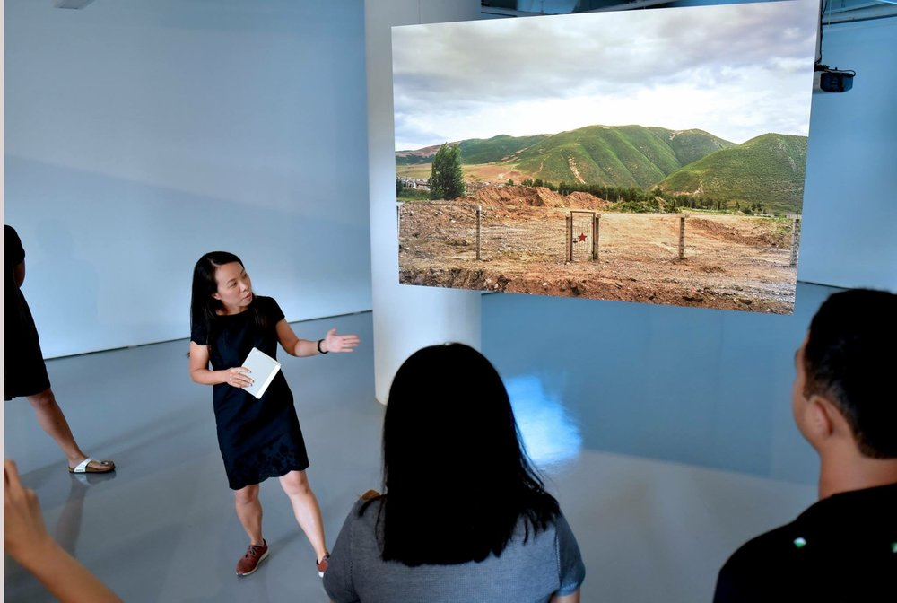 Chi Yin conducting a tour in front of her image that depicts fences along the China-North Korea border near the city of Tumen. Photo credit: Lim Sin Thai