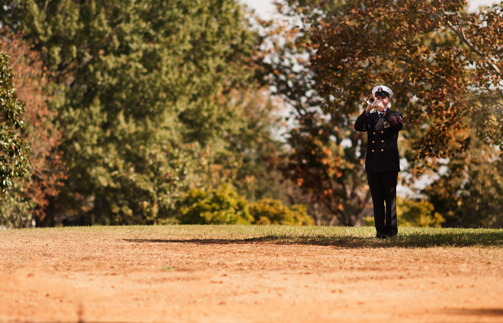 "WASHINGTON D.C., October 05, 2017-- A single bugle player sounds off ""Taps"" during a military funeral. The solemn melody resounds through the otherwise quiet cemetery-- even the birds are silent as it plays.  Photo by Taylor Mickal."