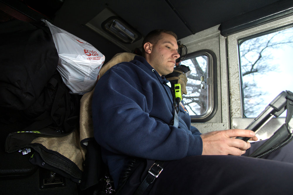 WASHINGTON D.C., December 22nd, 2017-- Technician Green utilizes the DC Fire and EMS tablet system to write up his patient assessment. The system contains vitals, interventions, and other meaningful data from the medical responses that are seamlessly transferred from the first responders to the ambulances who take the patients after transfer of care-- providing a quality continuity of care that is ultimately transferred to the hospitals where many patients will go.  Photo by Taylor Mickal.