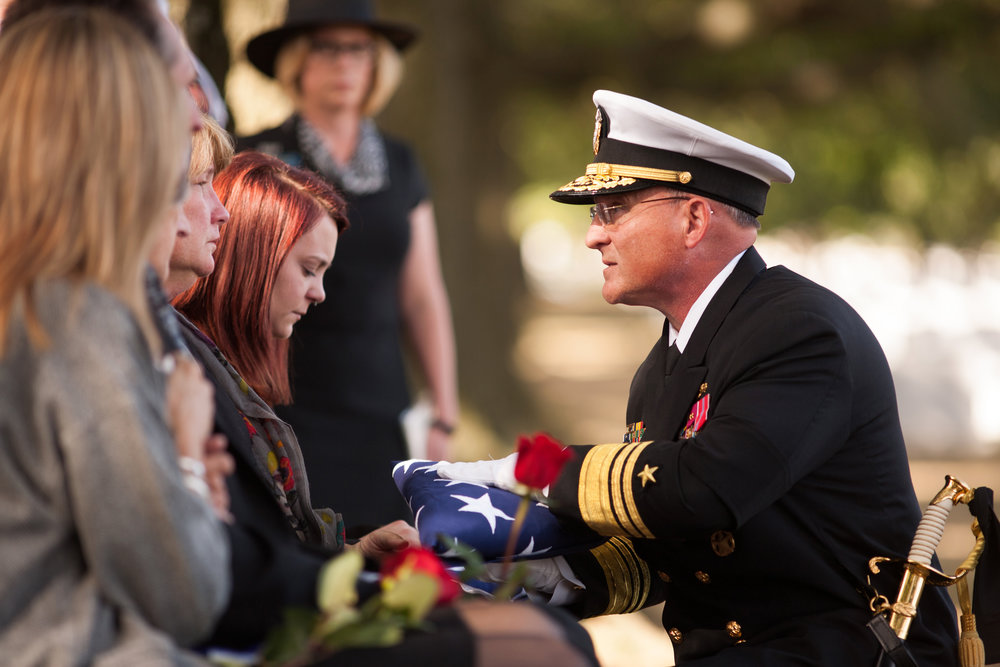 WASHINGTON D.C., October 05, 2017-- The first flag of three goes to the Kevin's wife. The admiral thanks her for his service to country and shares a few words in private condolence. The following two flags will go to his mother and father only moments later.  Photo by Taylor Mickal
