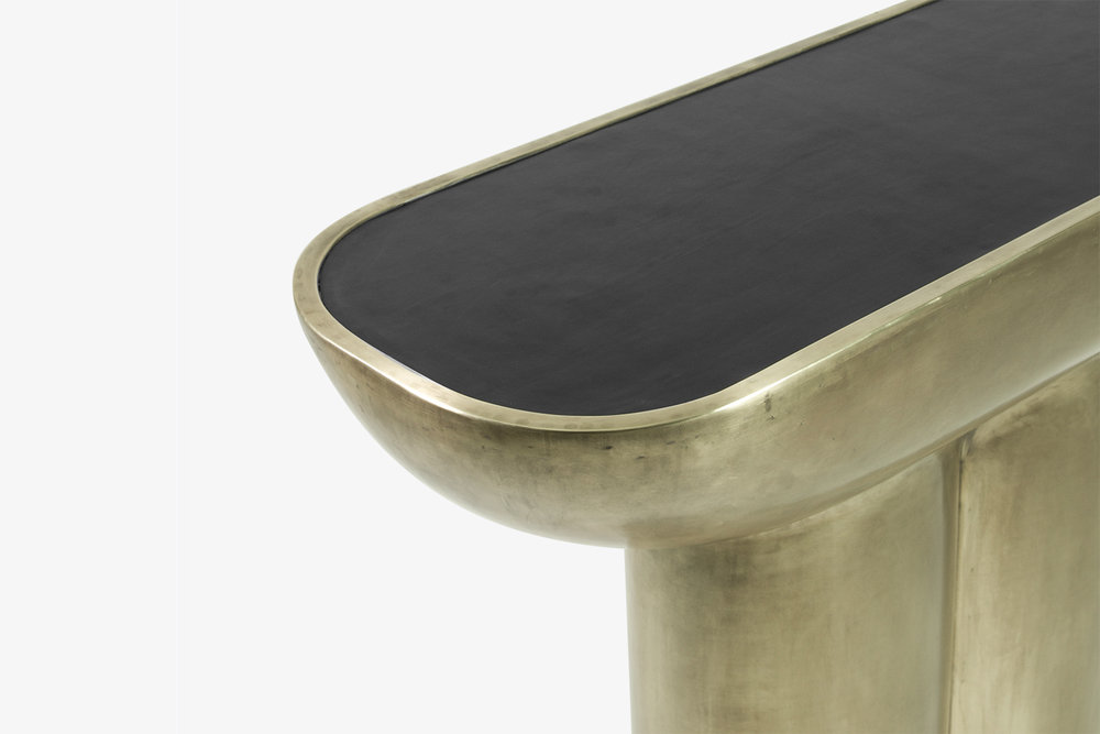 New console made with a single sheet of brass. Leather top.