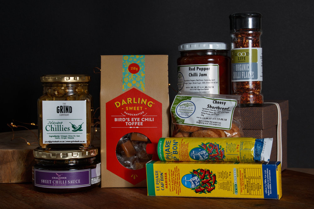 Sprigs Red Pepper Chilli Jam, Darling chilli toffee box, Bon Harissa paste tube, Chaloner sweet chillie sauce, Goodlife organic chillies flakes, cheesy shortbread cookies and The grind company Jalapeño Chillies. R430