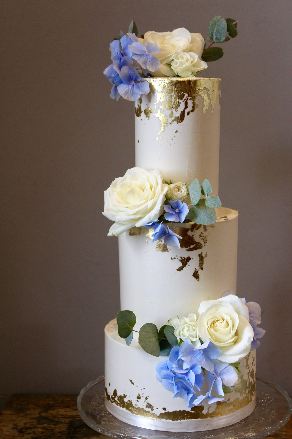 Modern three tier smooth buttercream with edible gold leaf.