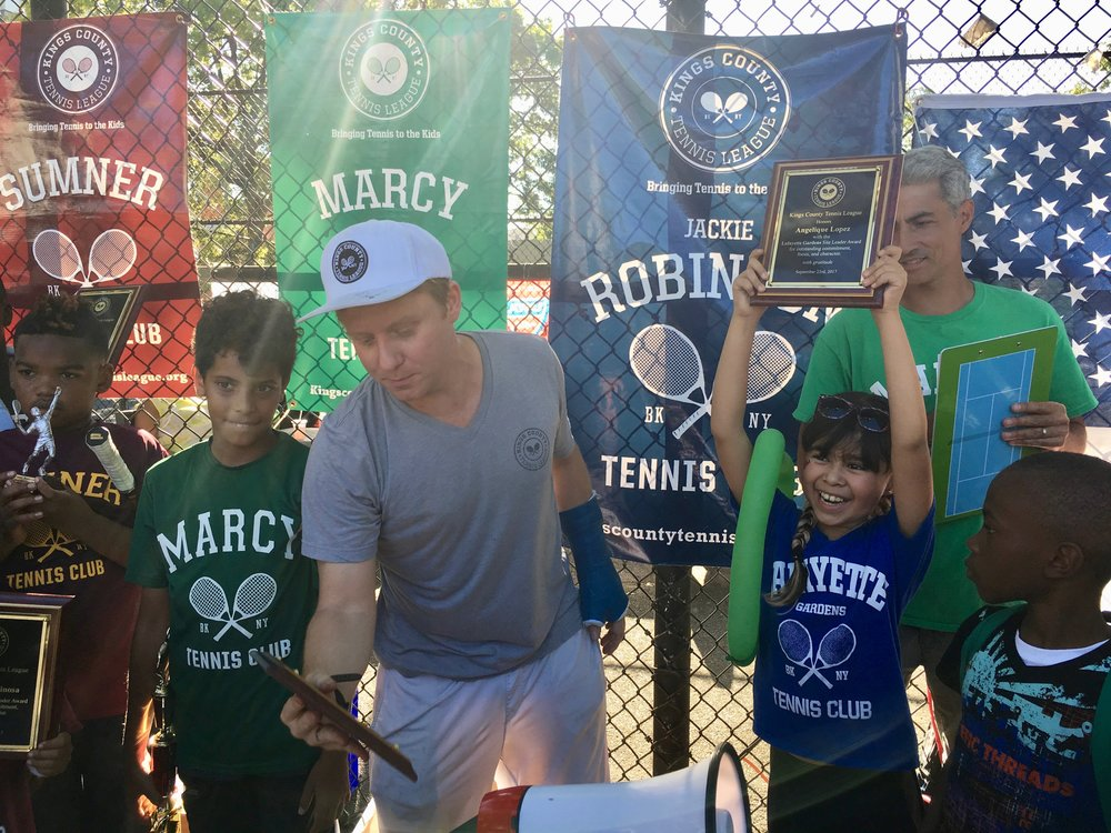 Michael McCasland, assisted by Marcy site leader, present trophies to the winners of the tournament and the kids who best embody KCTL principles.