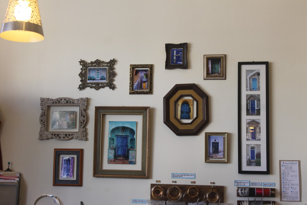 A gallery of blue door photos hang behind the cash wrap