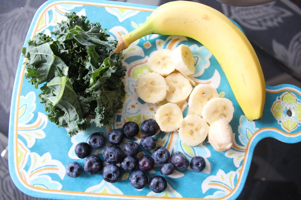 fruits and kale on blue cutting board
