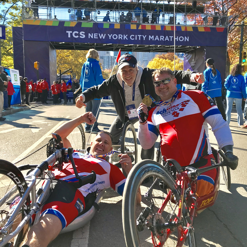 Achilles Freedom Team members Jess Walton and John Masson celebrating their NYC Marathon finish with Jon Stewart!
