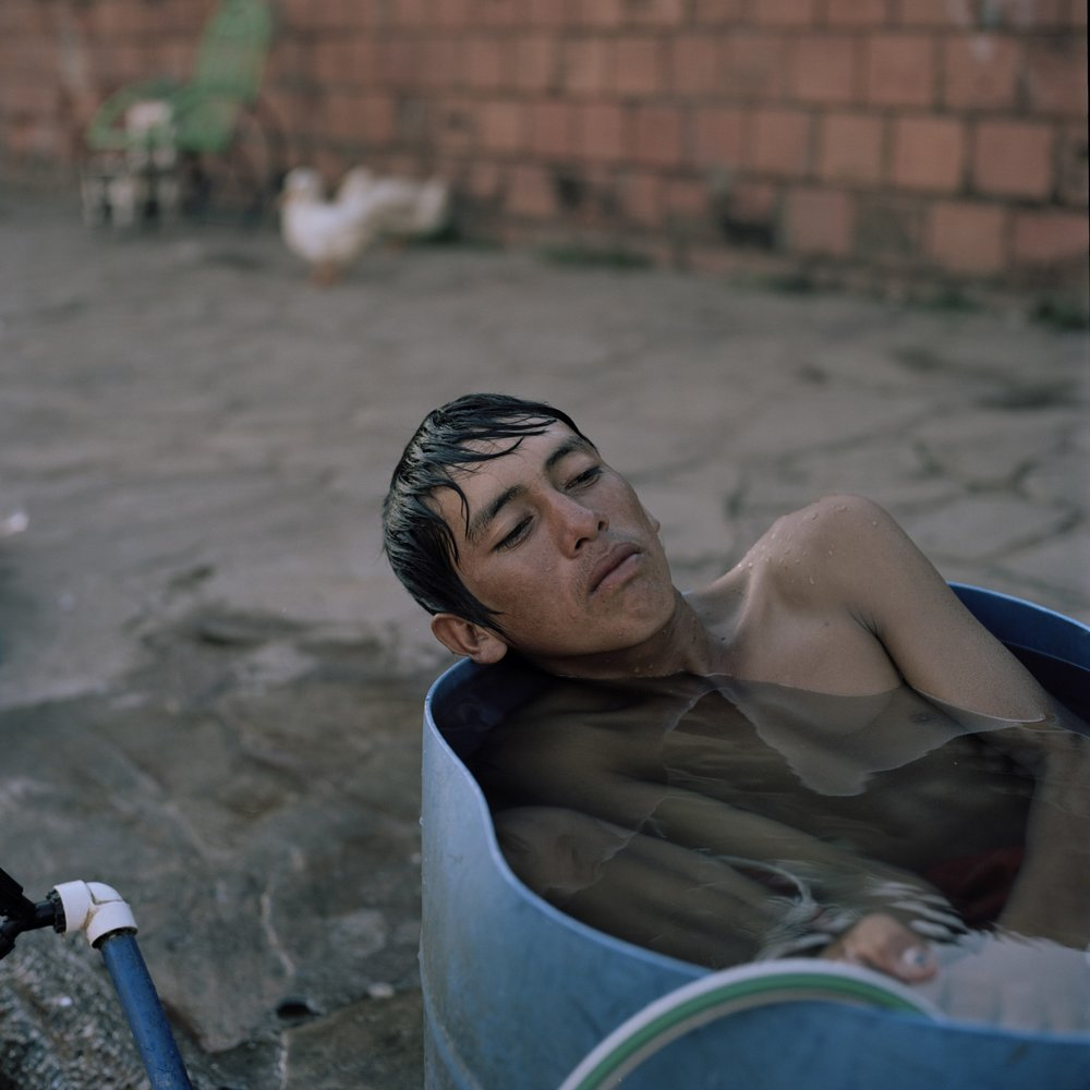 """Juan Ramón, 16, takes a bath on a barrel in front of their makeshift home in the streets of Asunción where he has been for eight months together with his family. They were living in the """"bañado"""", the area surrounding the river until recent floods resulting from El Niño, as well as deforestation due to agribusiness further up the river forced them to evacuate."""