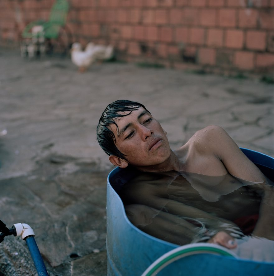 - 'Juan Ramón, 16, takes a bath in a barrel in the streets of Asunción, where he has lived with his family for eight months. They were living in the bañado, the area surrounding the river, until recent floods resulting from El Niño as well as deforestation due to agribusiness forced them to evacuate'
