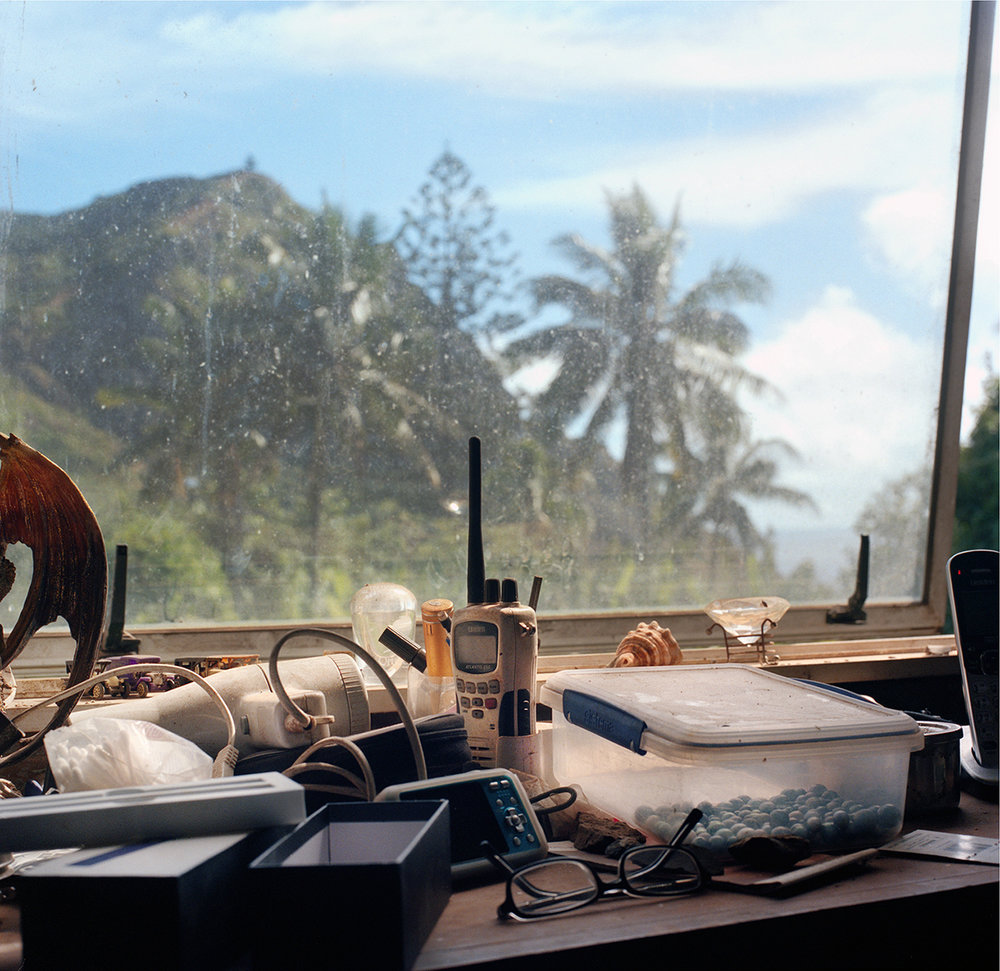 """Channel 16 and Black Pearls, Sue and Pawl's Window. From almost every home, the view of Christian's Cave can be seen. This is the window of Sue O'Keefe and Pirate Pawl. It sits between their computer desks, cluttered and dusty. The VHF radio sits at the centre of the haphazard arrangement, a device used as the islanders' mobile phone. If you run into problems on Pitcairn, the VHF is your only lifeline. Everyone is on island tuned to Channel 16 and is called by their first name only – """"Pawl, pawl"""" – the radio will crackle. In homes across the island, hands reach for their own radios to switch channel as the conversation moves over, eager to eavesdrop on proceedings. The grapevine on island is very short, understandable when news is in such short supply. From Big Fence / Pitcairn Island © Rhiannon Adam"""
