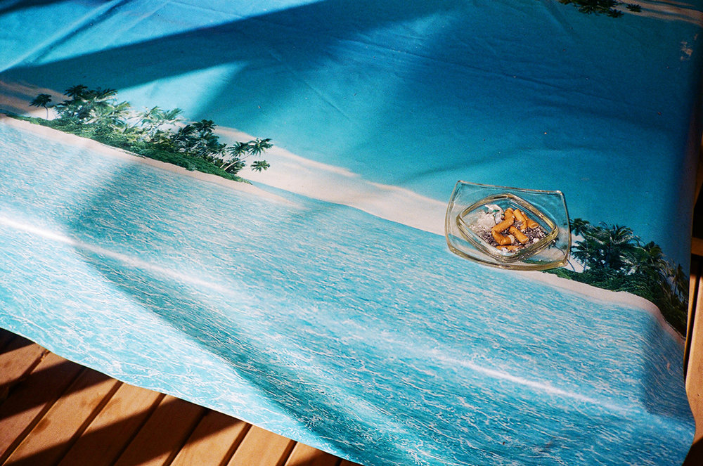 Waiting For Paradise, Down Flatcher. Down Flatcher is the home of Betty Christian. At one time, Betty ran a café from her home. This plastic tablecloth sits on the decked area, where her customers would sit. I couldn't help but be struck between that image of paradise, and the version that we were apparently living in. Pitcairn is the epitome of Paradise for so many, and yet the reality is starkly different. Even on Pitcairn Island, the grass is greener elsewhere. From Big Fence / Pitcairn Island © Rhiannon Adam