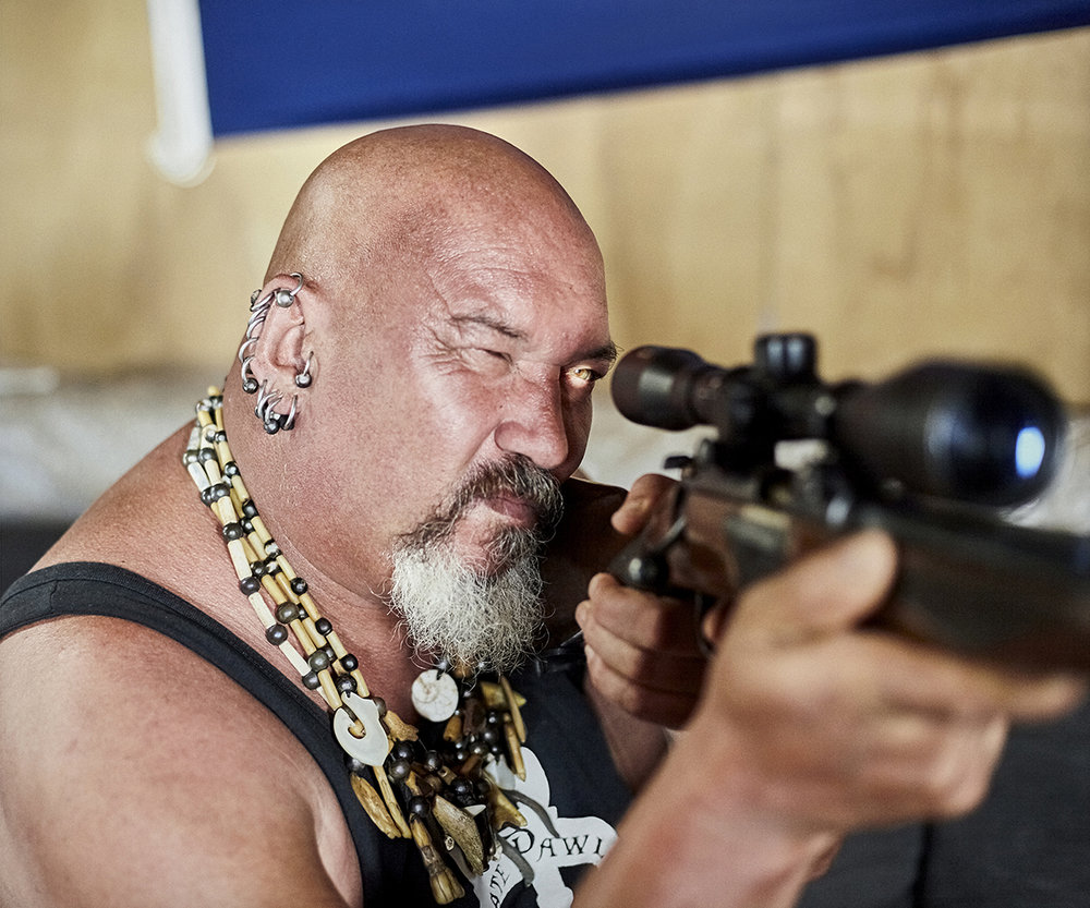 """Pawl Warren takes aim. 'Pirate' Pawl Warren is a gentle giant. He calls his home """"Switzerland"""" as only there are you are free to speak openly. It was a friend of his daughter who first reported a sexual assault by an off islander (Ricky Quinn) to visiting Kent police officer, PC Gail Cox, after a party at Pawl's house. This single action brought Pitcairn's sexual abuse problems to the surface. Pawl has been steadfast in his support of the island women, and I'm lucky to call him my friend. He is one of the few islanders able to hold a gun licence. Licences were revoked for all convicted men when the trials took place, largely for fear of suicide. Pawl uses his gun to shoot down breadfruit, a large green starchy fruit, a staple dietary item in Polynesia, and the cause of the Bounty's original mission. Though Pawl, by his own admission, said that there are a few other places that he would rather point his gun than at the Mutiny fruit alone. From Big Fence / Pitcairn Island © Rhiannon Adam"""
