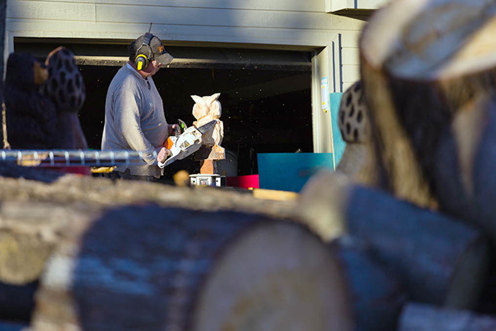 CORY MACNEIL/Citizen photo TJ Jenkins works on carving an owl with his chainsaw outside his home in rural Platte County. With no formal training, he has developed a passion, and business, for his unique wood art. He's also working to make it a full-time job, employing different techniques to make his work cost-efficient.