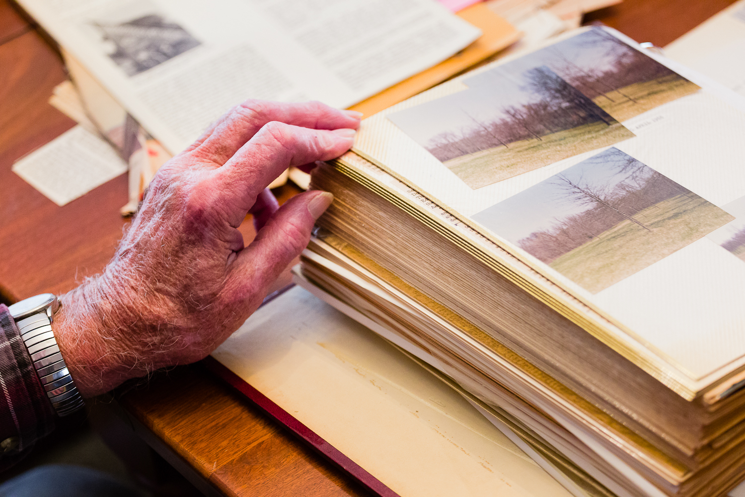 CORY MACNEIL/Citizen photo Donald Swanstone, Sr. flips through a photo album from his time as site manager for the camp. He served in that role for nearly two decades, part of a family lineage that helped upkeep the camp during its storied history.