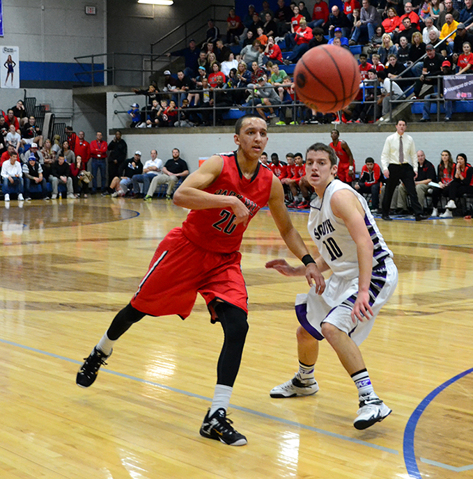 BRYCE MERENESS/Citizen photo Park Hill guard Landry Shamet, left, passes around the defense of Park Hill South guard Mitch Henderson during the Class 5 District 16 championship game on Friday, March 6 at Central High School in St. Joseph, Mo.