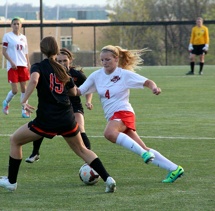 BRYCE MERENESS/Citizen photo Park Hill midfielder Madi Massa (4) attempts to dribble past Platte County defender Kelsey Evans (19) during a game Thursday, April 16 at Park Hill District Soccer Stadium in Riverside, Mo.